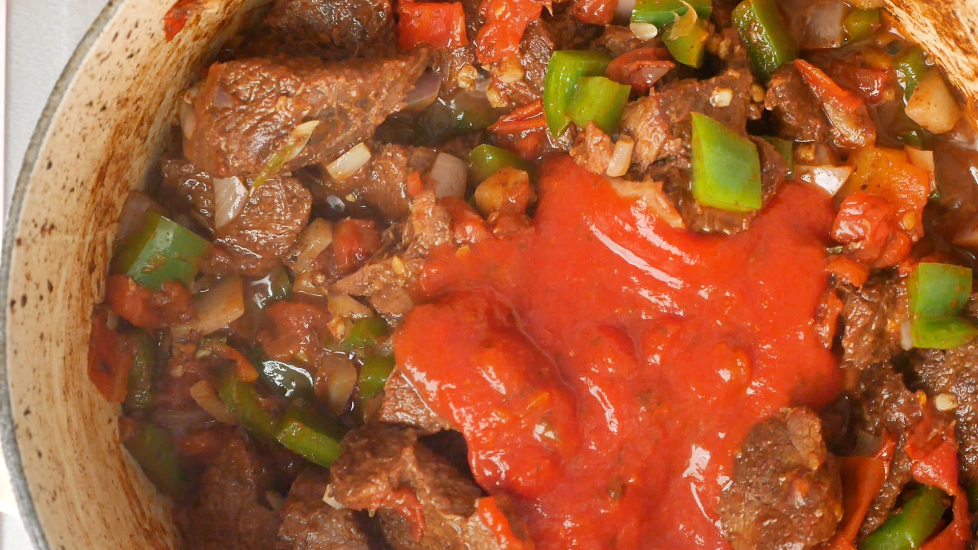 Adding tomato sauce to meat