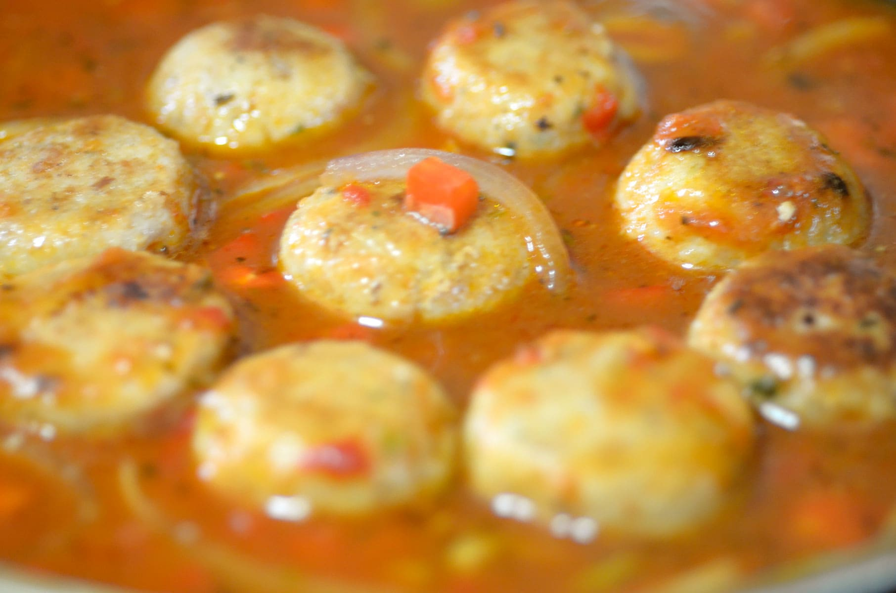 Fishballs cooking in tomato sauce