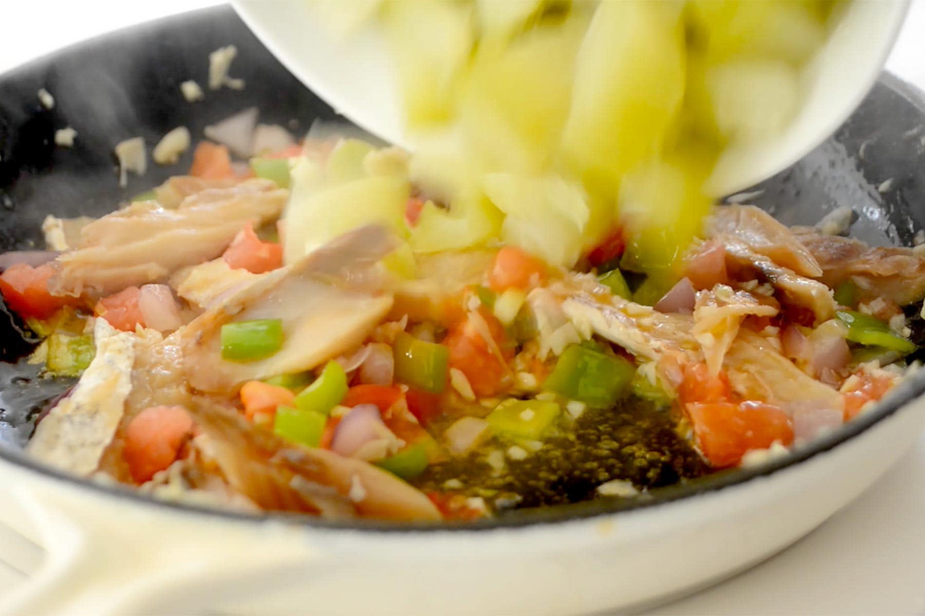 Adding chayote to pot with codfish