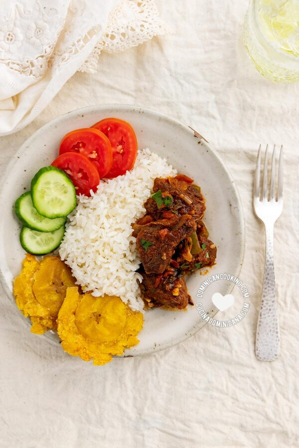 Carne de Res Guisada (Dominican Braised Beef) served with to rice, tostones, and salad
