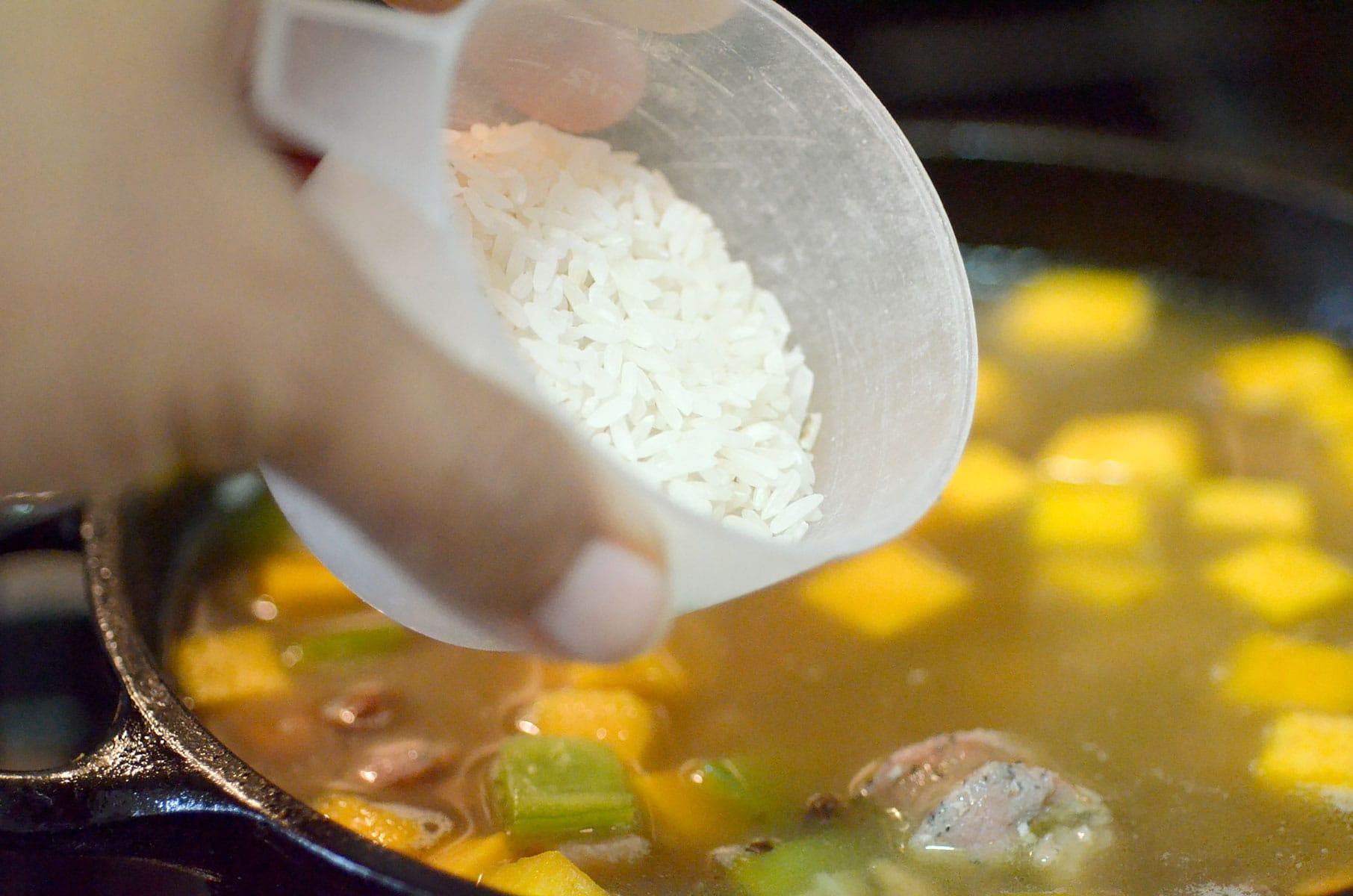 Adding raw rice to pot