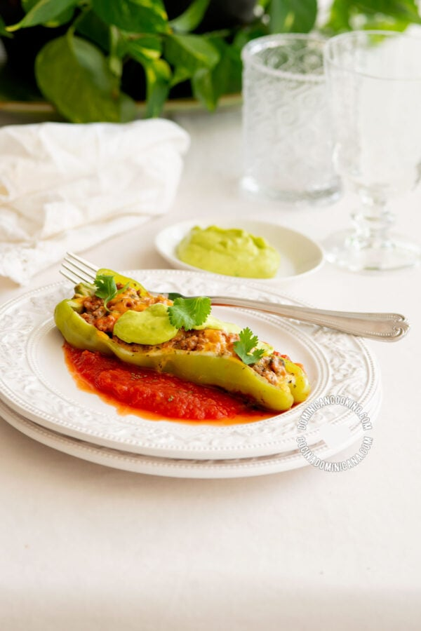 Plate with pepper boat on tomato sauce and bowl with avocado sauce