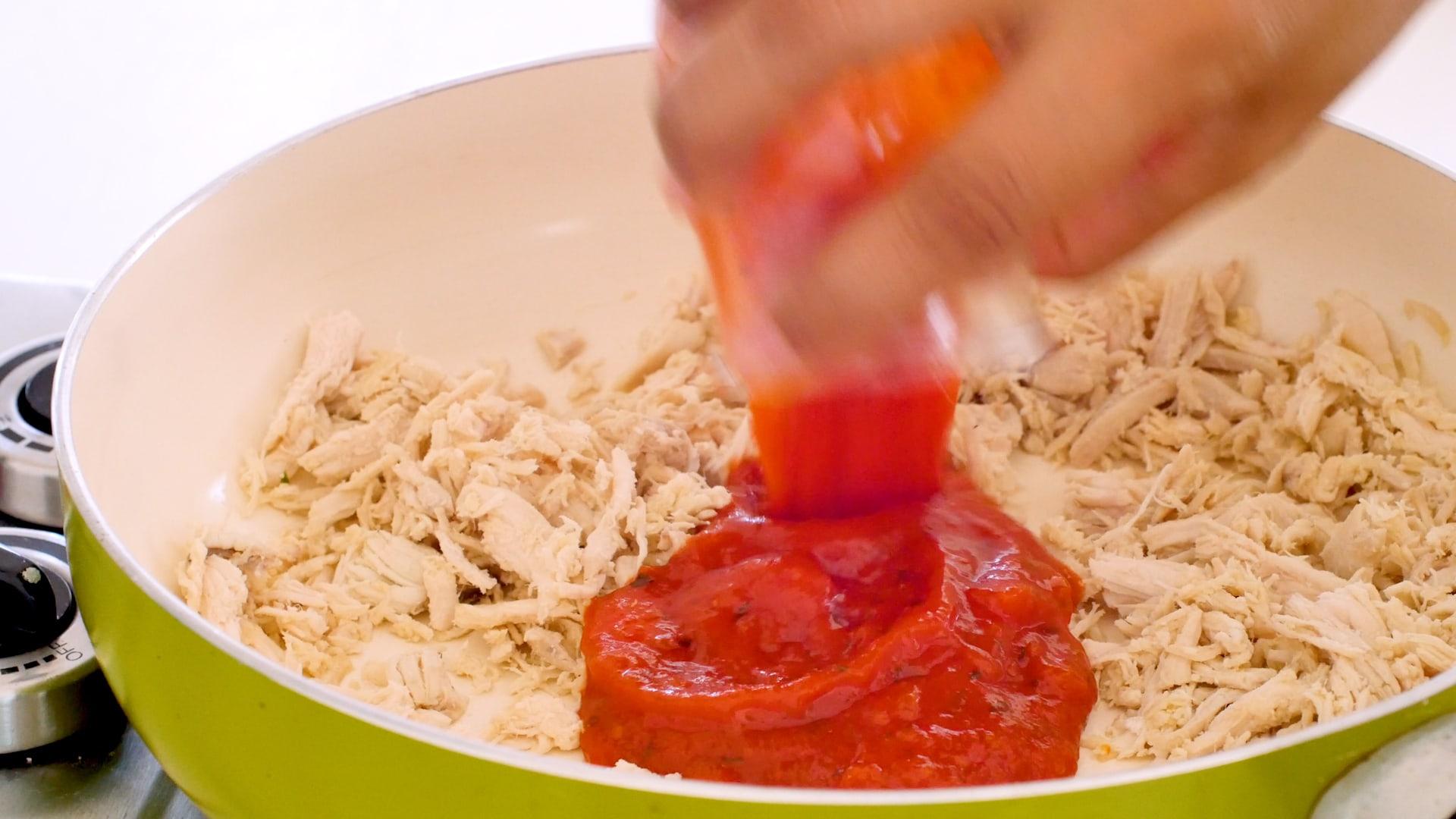 Adding tomato sauce to chicken