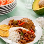 Dominican dish of rice, beans and chicken served with salad and avocado