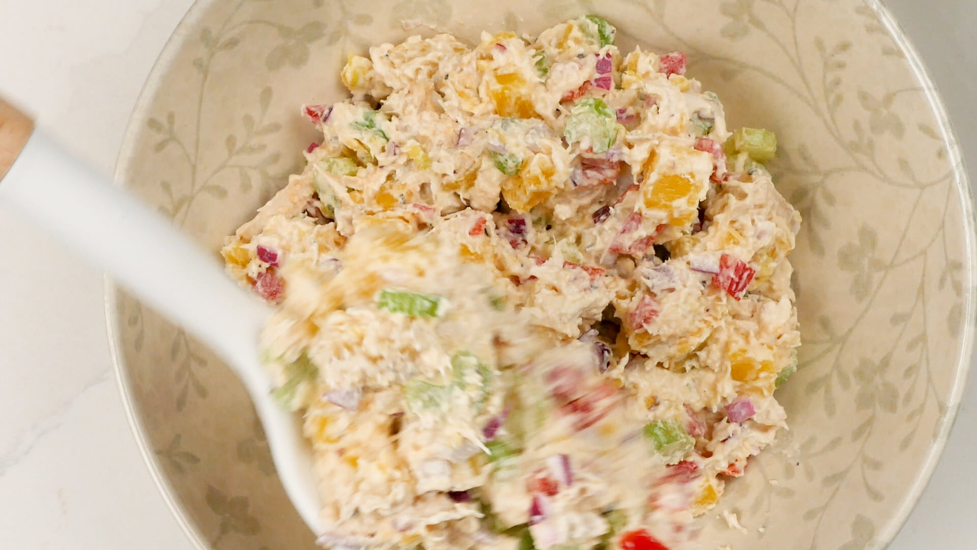 Scooping potato and chicken salad onto a plate
