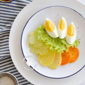 Ensalada Hervida (Boiled Salad) served alongside vinaigrette seen from above