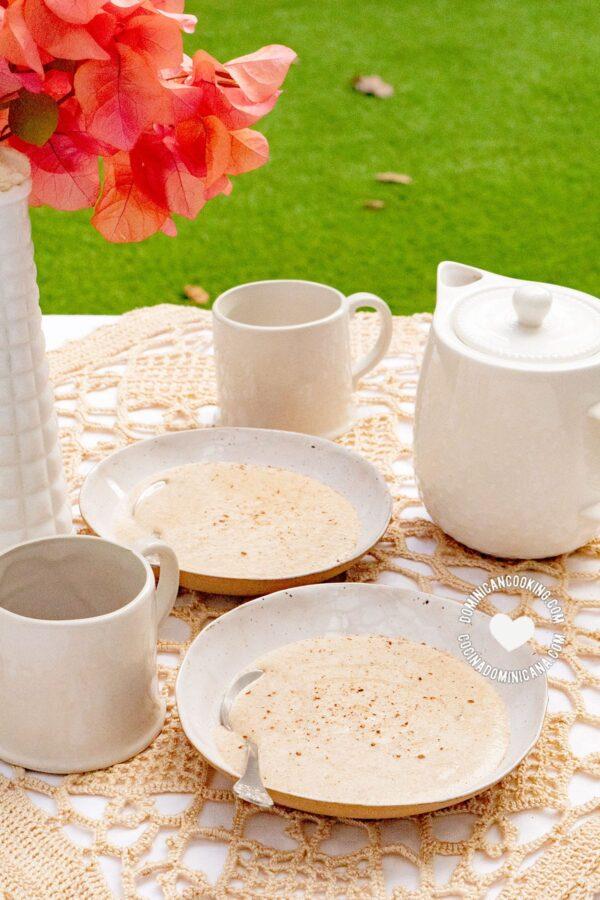 Dominican-Style Farina: Spiced Cream of Wheat Porridge en mesa de jardín con tazas de café
