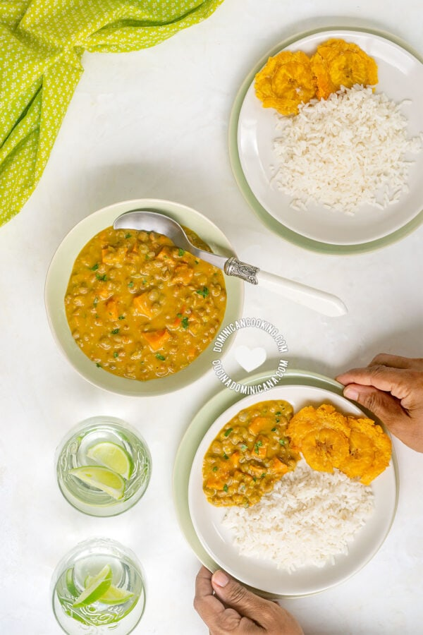 Hands holding bowl of Guandules con Coco (Pigeon Peas with Coconut)