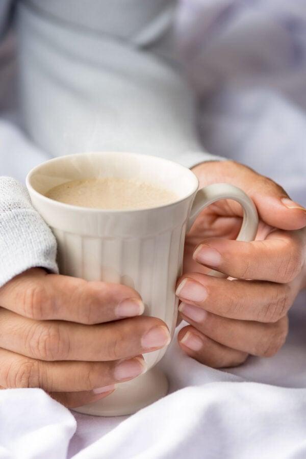 Hands holding a Cup of Ponche de Desayuno (Breakfast Eggnog)