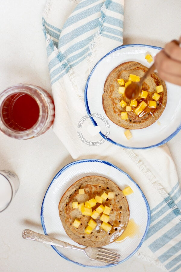 Pouring honey on Whole Wheat and Banana Sugar-Free Pancakes