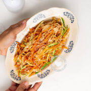 Hands holding plate with green papaya salad
