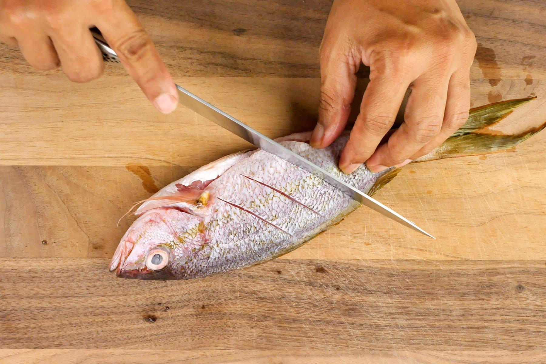 Making diagonal cuts into the fish