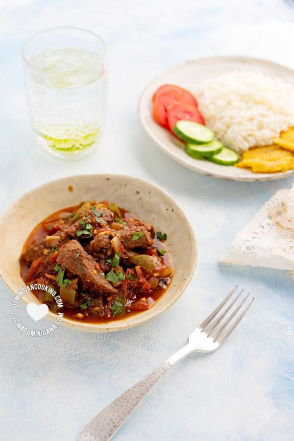 Carne de Res Guisada (Dominican Braised Beef) served next to rice, tostones, and salad