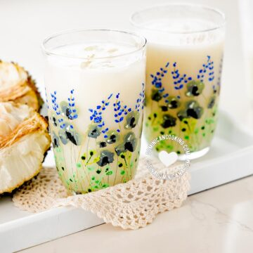 Champola de guanábana in two glasses, plus fruit.