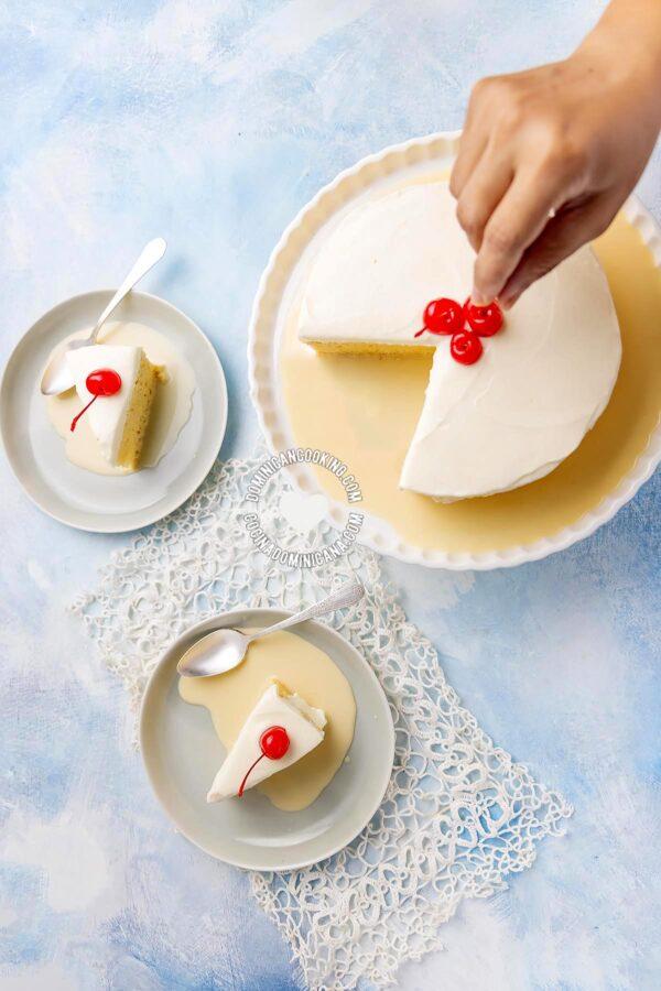 Hand putting cherry on Tres Leches (Three-Milk Cake)