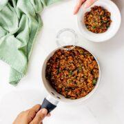Pot and bowl of lentil and mushroom vegan stuffing for empanadas